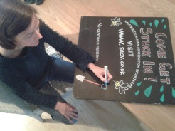 Volunteer working on SACV chalkboard